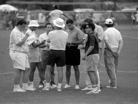 Mayo (dark shirt, on right) gets the scoop from Don Shula (center), circa 1990. Photography: Miami Dolphins.