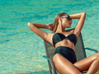 Bellini Top by Montce Swim, $98, available at Montce Swim. Black High Rise Bikini Bottom by Montce Swim, $72, available at Montce Swim. Black Wrap Sunglasses by Valentino, $300, available at Sunglass Hut.