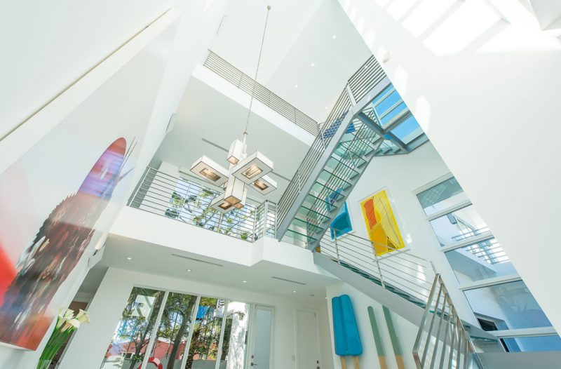 The glass staircase allows the artworks displayed on each floor to be seen from any floor. Photography by Eric Igualada, Spectrum Aerial Video & Photography